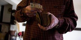 Mann mit Portmonnaie und Gelschein in der Hand