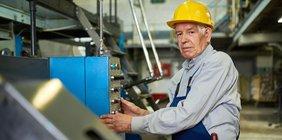 älterer Fabrikarbeiter mit Helm und Overall bedient eine Maschine