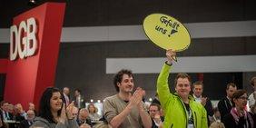"""Mann hält Schild mit Aufschrift """"Gefällt uns"""" hoch; Hintergrund: Kongress, großes DGB-Logo"""