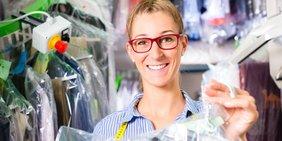 Lächelnde Frau in der Reinigung mit frisch gereinigten Hemden